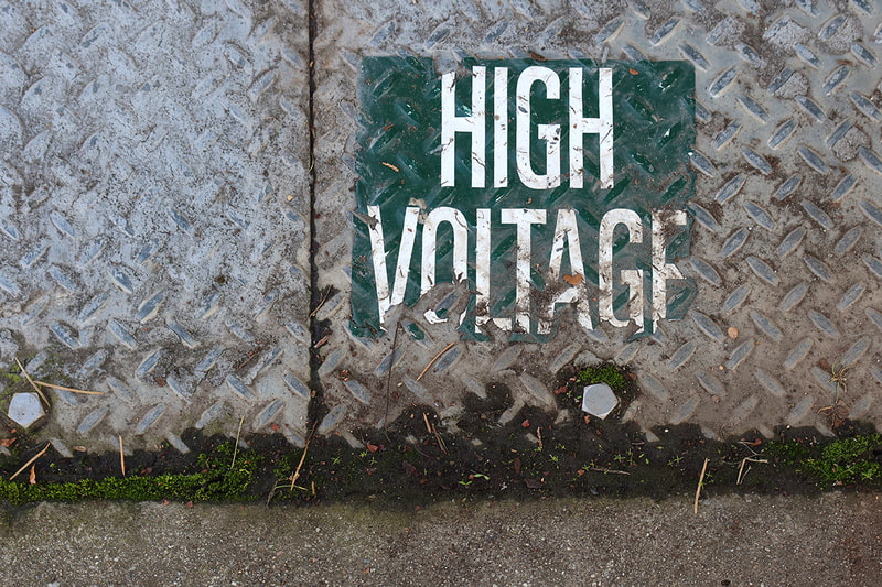 green door with high voltage sign