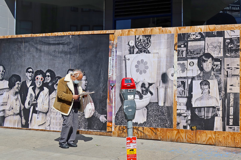 man walking in front of Michael Jang mural
